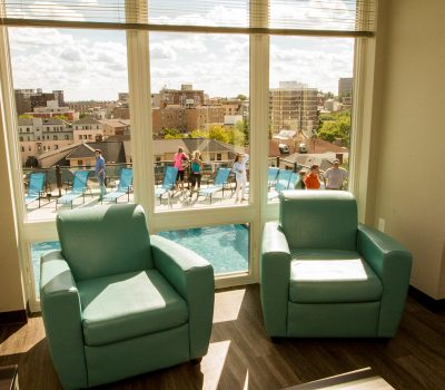 View of People in Pool From Apartment Living Room